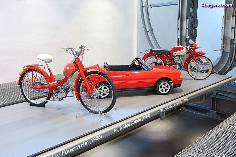 """Die Zweiräder NSU Quickly """"Feuerwehr"""" und """"Cavallino"""" sowie das Audi Cabriolet im Maßstab 1:2 sind auf einer Plattform präsentiert."""